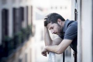 Depression - Man leaning on balcony railing holding hand on head depressed thinking.
