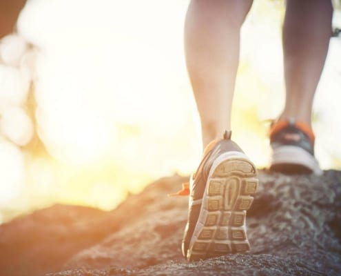 Mental Health Exercise - Person Jogging, Blurred Background, Showing Sneakers.