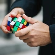 Mental Health Solving Problems - Man with ruby cube working out problems concept.