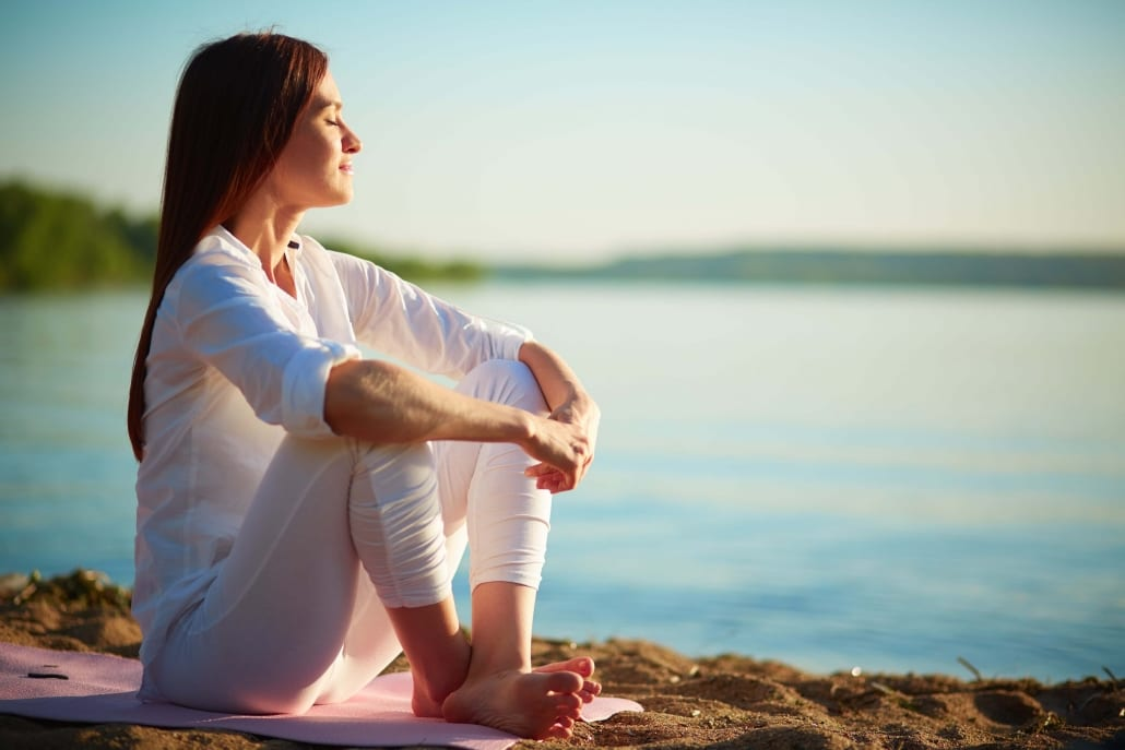 Tone The Vagus Nerve - Woman Sitting Meditating On Sand at the shore of the lake.