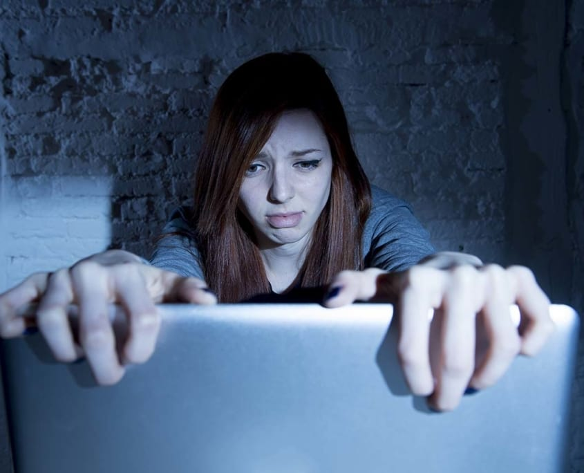 Anxiety - Girl with anxiety looking at social media on computer screen.
