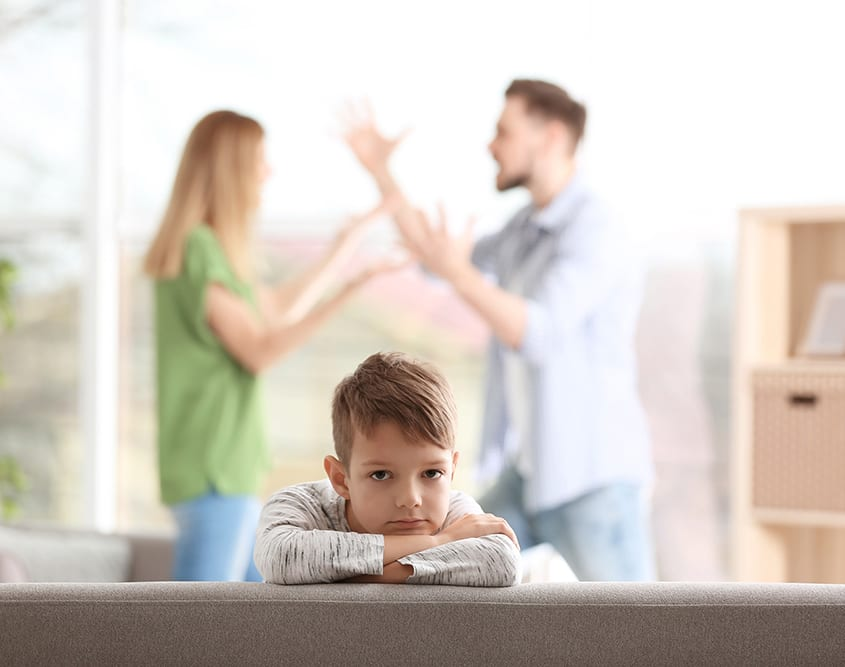 Little unhappy boy sitting on sofa while parents arguing at home - Counselling Services Melbourne